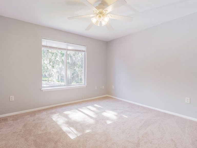 CountrySide at the University apartment interior - carpeted bedroom with ceiling fan